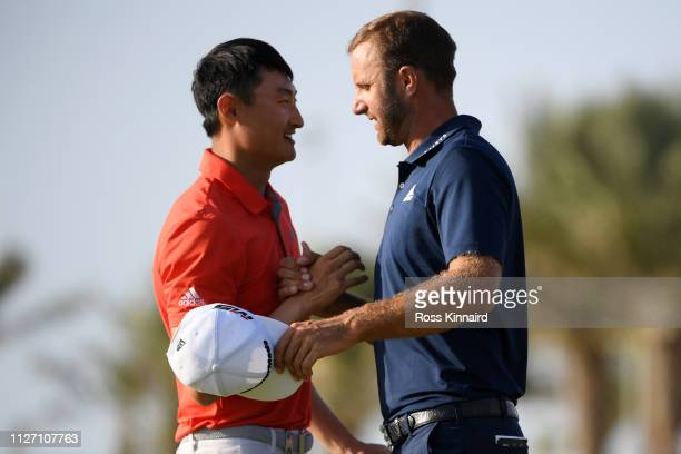 Dustin Johnson of The United States shakes hands with Li Haotong of China on the 18th hole during Day four of the Saudi International at the Royal...