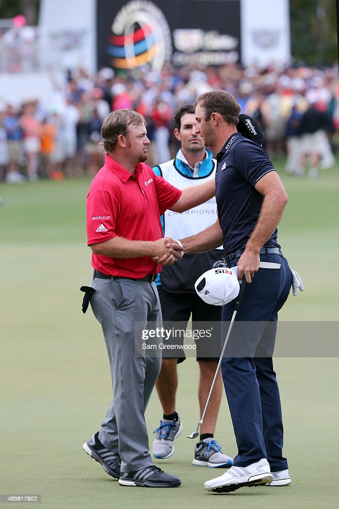 Dustin Johnson (R) of the United States shakes hands with second place J. B. Holmes (L) of the United States on the eighteenth hole green after winning the World Golf Championships-Cadillac Championship at Trump National Doral Blue Monster Course on March 8, 2015 in Doral, Florida.