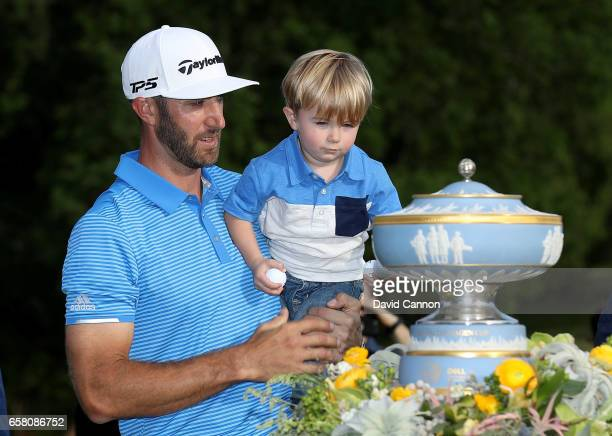 Dustin Johnson of the United States shows the Walter Hagen Trophy to his young son Tatum after his 1 up win in his match against John Rahm of Spain...