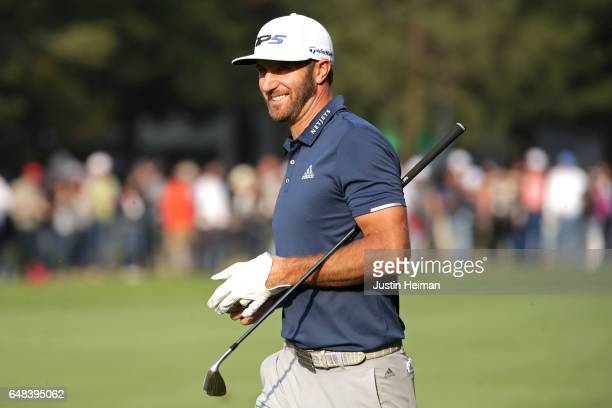 Dustin Johnson of the United States smiles after playing his second shot on the 18th hole during the final round of the World Golf Championships...