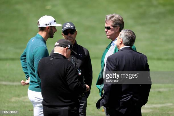 Dustin Johnson of the United States talks to Augusta National member Fred Ridley on the practice range prior to announcing his withdrawl during the...