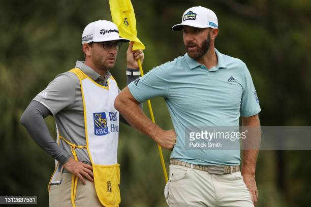 Dustin Johnson of the United States talks with his caddie and brother, Austin Johnson, on the 13th green during the first round of the RBC Heritage...