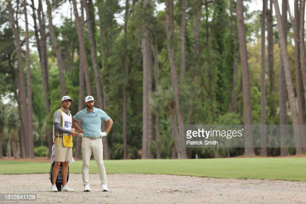Dustin Johnson of the United States talks with his caddie and brother, Austin Johnson, on the 15th hole during the first round of the RBC Heritage on...
