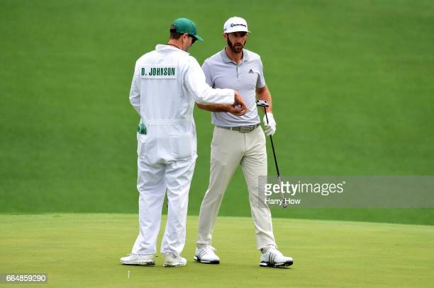 Dustin Johnson of the United States talks with his caddie Austin Johnson on the tenth hole during a practice round prior to the start of the 2017...