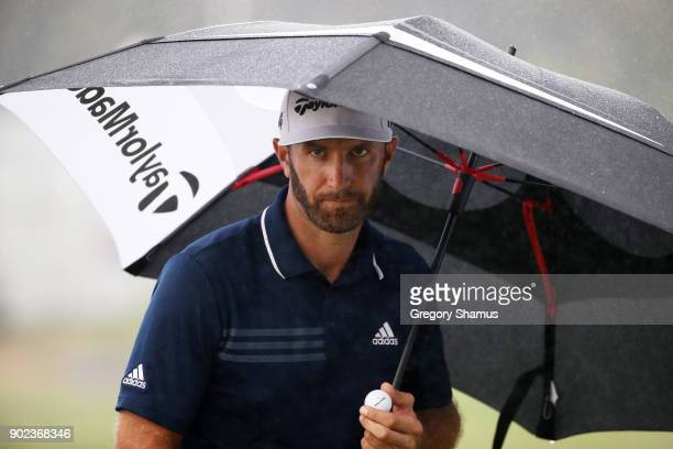 Dustin Johnson of the United States uses an umbrella as he walks to the 15th tee during the final round of the Sentry Tournament of Champions at...