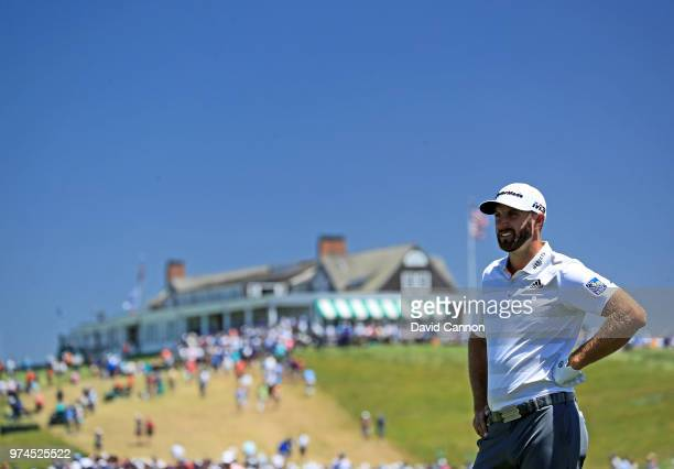 Dustin Johnson of the United States waits to walk to the green after playing his second shot on the first hole during the first round of the 2018 US...