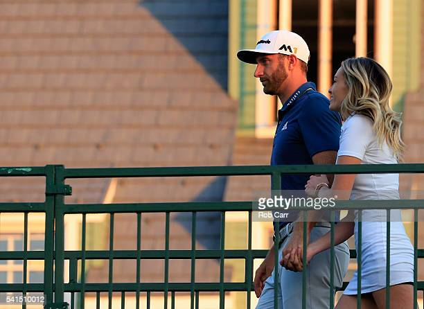 Dustin Johnson of the United States walks to the 18th green with partner Paulina Gretzky after winning the US Open at Oakmont Country Club on June 19...