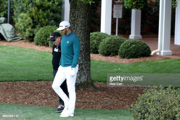 Dustin Johnson of the United States walks with coach Butch Harmon to the practice range during the first round of the 2017 Masters Tournament at...