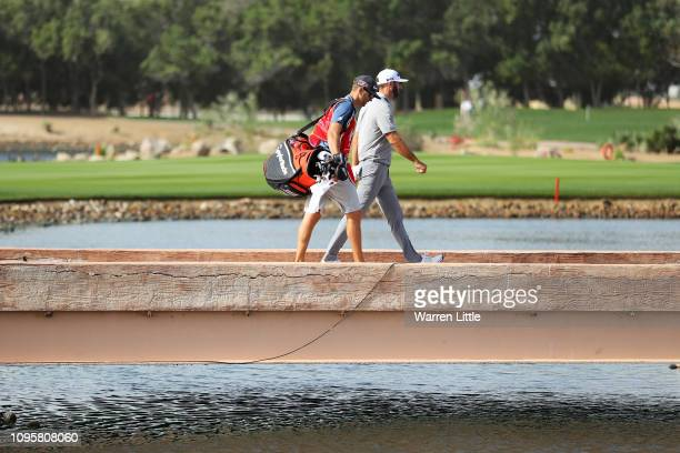 Dustin Johnson of the United States walks with his caddie and brother Austin walk across the bridge to the seventh tee during Day Three of the Abu...