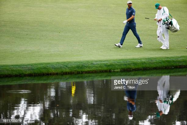 Dustin Johnson of the United States walks with his caddie Austin Johnson on the 16th hole during the second round of the Masters at Augusta National...
