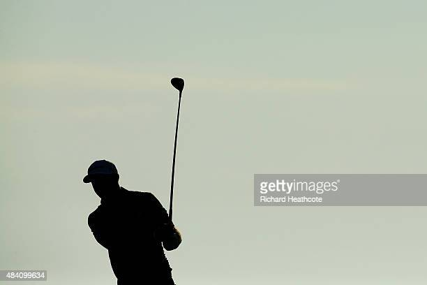 Dustin Johnson of the United States watches his tee shot on the 18th hole during the continuation of the weather-delayed second round of the 2015 PGA...