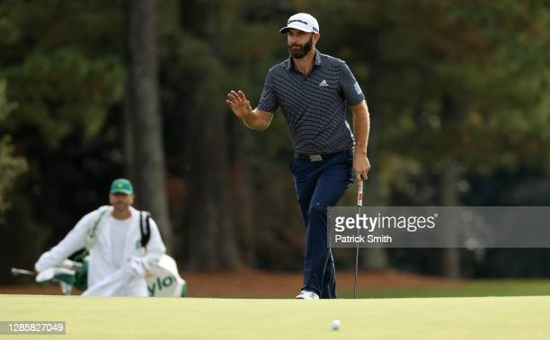 Dustin Johnson of the United States waves as he walks to the 18th green during the final round of the Masters at Augusta National Golf Club on...