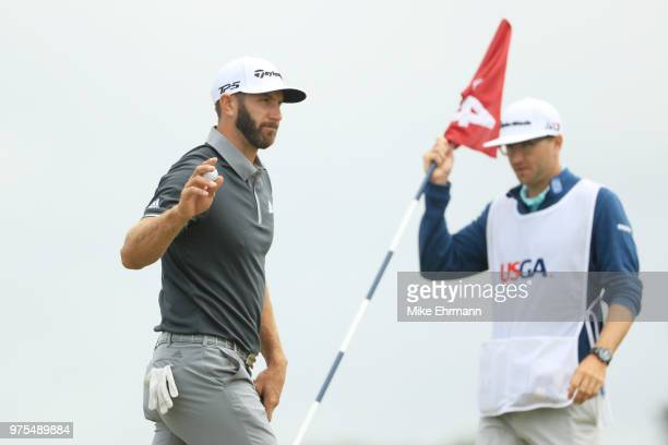 Dustin Johnson of the United States waves to the crowd after making a birdie on the fourth hole as caddie Austin Johnson looks on during the second...