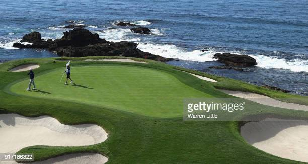 Dustin Johnson of the USA acknowledges the crowd on the seventh green during the final round of the ATT Pebble Beach ProAm the Pebble Beach Golf...