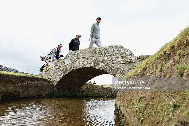 Dustin Johnson of the USA and Hideki Matsuyama of Japan walk across the Swilcan Bridge during the first round of the 144th Open Championship at The...