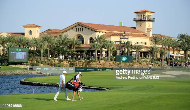 Dustin Johnson of the USA and his caddie Austin Johnson walk down the 18th hole on Day Three of the Saudi International at Royal Greens Golf and...