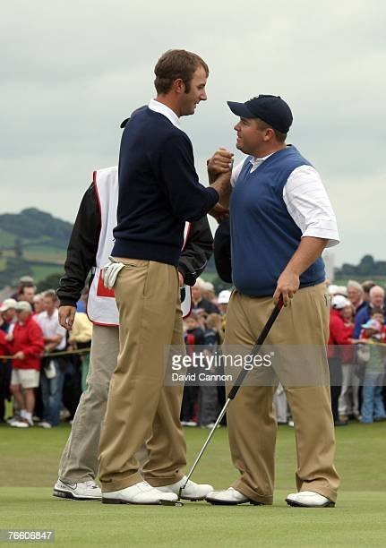 Dustin Johnson of the USA celebrates victory with his partner Colt Knost of the USA before he hits his tee shot on the 18th green during the morning...