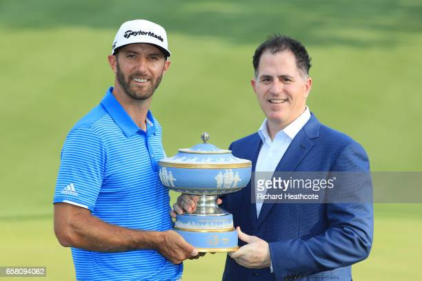 Dustin Johnson of the USA is presented with the trophy by Michael Dell Chairman and CEO of Dell Technologies after winning the World Golf...