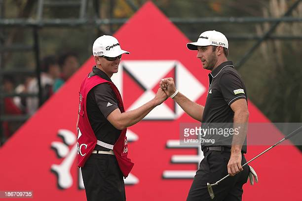 Dustin Johnson of the USA with his caddy celebrates after chiipping in for an eagle on the 16th hole during the final round of the WGC HSBC Champions...