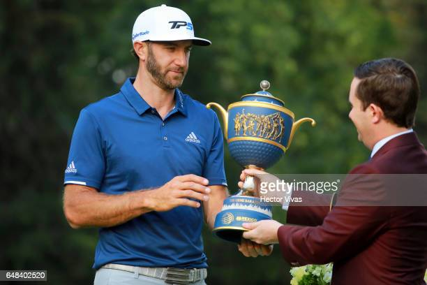 Dustin Johnson of United States receives the trophy during the final round of the World Golf Championships Mexico Championship at Club De Golf...