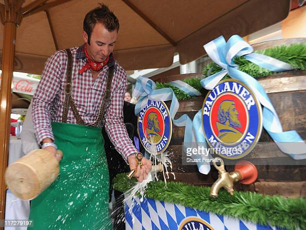 Dustin Johnson of USA knocks a spout in the beer keg as he wears the traditional lederhosen costumes at the player party after the second round of...