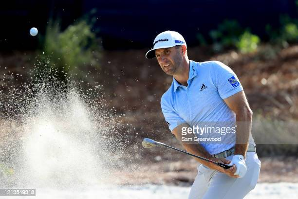 Dustin Johnson plays a shot on the 14th hole during the first round of The PLAYERS at the TPC Stadium course on March 12 2020 in Ponte Vedra Beach...