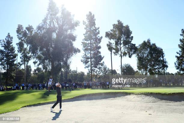 Dustin Johnson plays his shot from the bunker on the second hole during the second round of the Genesis Open at Riviera Country Club on February 16...