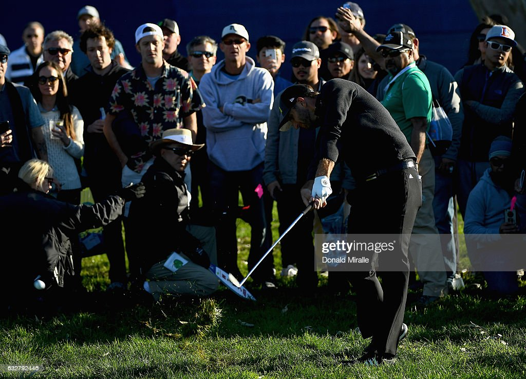 Dustin Johnson plays his shot out of the rough on the 18th hole during the first round of the Farmers Insurance Open at Torrey Pines South on January 26, 2017 in San Diego, California.