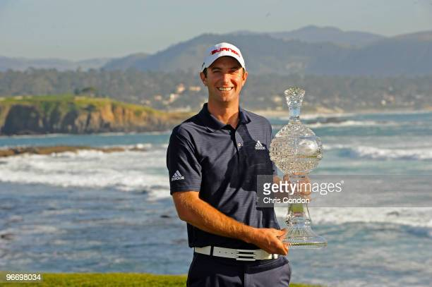 Dustin Johnson poses with the tournament trophy after winning the ATT Pebble Beach National ProAm at Pebble Beach Golf Links on February 14 2010 in...
