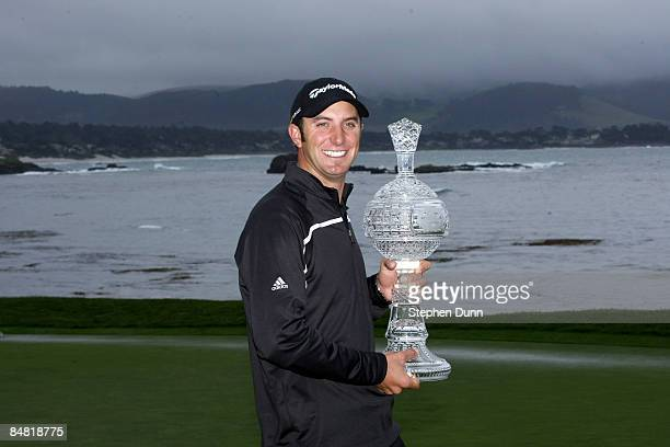 Dustin Johnson poses with the trophy on th e18th green at Pebble Beach Golf Links after cancellation of the final round of the the ATT Pebble Beach...