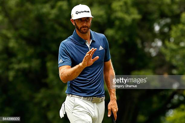 Dustin Johnson reacts after putting for birdie on the second green during the final round of the World Golf Championships Bridgestone Invitational at...