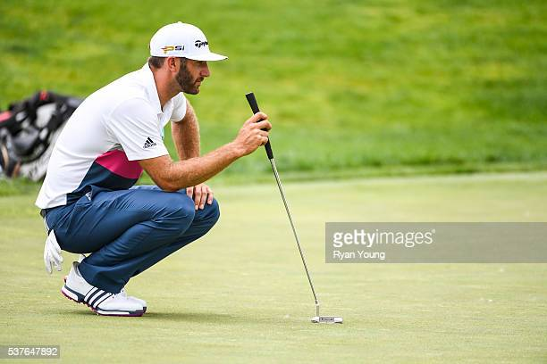 Dustin Johnson reads his putt with his Scotty Cameron by Titleist Newport 2 putter on the 18th hole green during the first round of the Memorial...