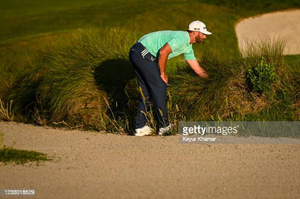 Dustin Johnson searches for his ball in the tall grass off the green on the 18th hole during the first round of the PGA Championship on The Ocean...
