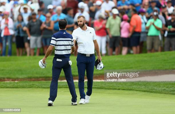 Dustin Johnson shakes hands with Nick Taylor of Canada on the 18th hole during the third round at the RBC Canadian Open at Glen Abbey Golf Club on...