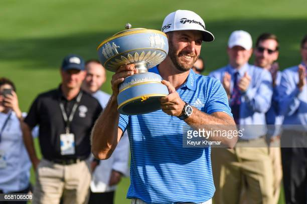 Dustin Johnson smiles and lifts the Walter Hagen Cup trophy following his 1up victory on the 18th hole green following the championship match at the...