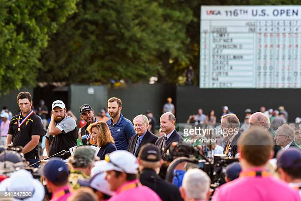 Dustin Johnson smiles during the trophy ceremony with, from left, Jon Rahm of Spain, Shane Lowry of Ireland, Scott Piercy, Jack Nicklaus and USGA...