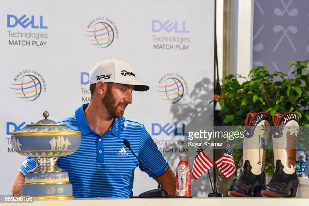 Dustin Johnson smiles while looking at the custom cowboy boots presented to the winner following his 1up victory in the championship match at the...