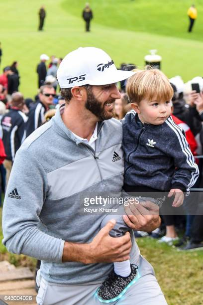 Dustin Johnson smiles with his son Tatum as he leaves the 18th hole green after his five stroke victory during the final round of the Genesis Open at...