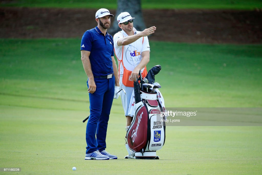 Dustin Johnson stands with his caddie during the final round of the FedEx St. Jude Classic at TPC Southwind on June 10, 2018 in Memphis, Tennessee.
