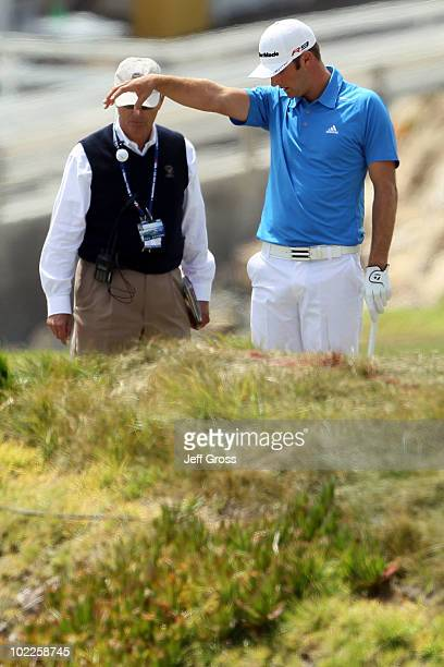 Dustin Johnson takes a penalty drop on the fourth hole alongside a USGA rules official during the final round of the 110th US Open at Pebble Beach...