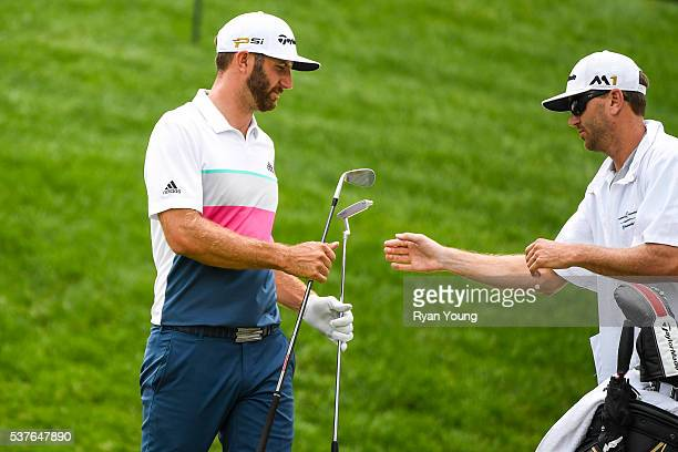 Dustin Johnson takes his Scotty Cameron by Titleist Newport 2 putter from caddie Austin Johnson on the 17th hole green during the first round of the...