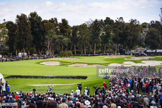 Dustin Johnson tees off on the 10th hole as fans watch during the final round of the Genesis Open at Riviera Country Club on February 19, 2017 in...