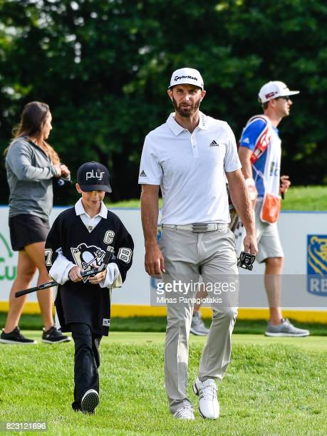 Dustin Johnson walks with a youngster on the seventh hole during the championship proam of the RBC Canadian Open at Glen Abbey Golf Course on July 26...