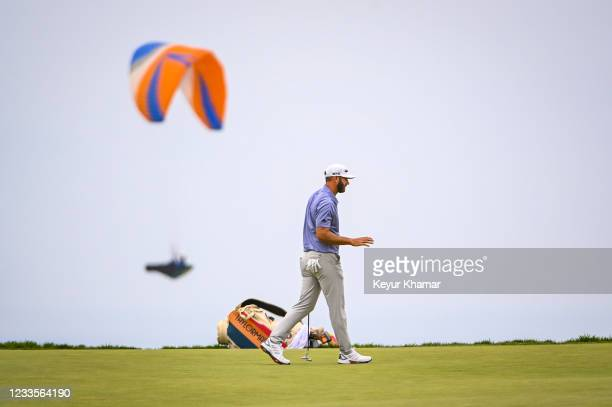 Dustin Johnson waves after making a par putt on the 12th hole green as a paraglider flies by during the third round of the 121st U.S. Open on the...