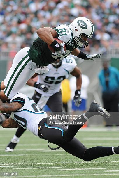 Dustin Keller of the New York Jets caries the ball and is upended during a NFL game against the Jacksonville Jaguars at Giants Stadium on November 15...