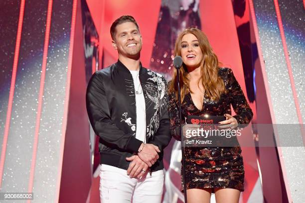 Dustin Lynch and Isla Fisher speak onstage during the 2018 iHeartRadio Music Awards which broadcasted live on TBS TNT and truTV at The Forum on March...