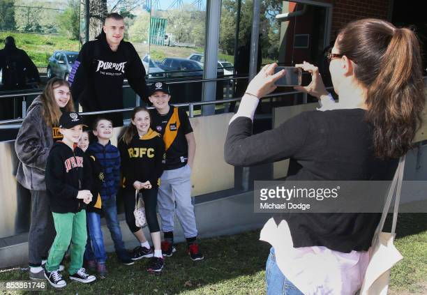 Dustin Martin, a winner of the Brownlow medal last night, poses with young Tigers fans ahead of the Richmond Tigers AFL training session at Punt Road...