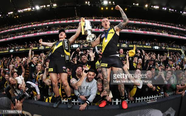 Dustin Martin and Liam Baker of the Tigers celebrate victory with the Premiership Trophy and fans during the 2019 AFL Grand Final match between the...