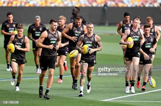 Dustin Martin and team mates run during a Richmond Tigers AFL training session at The Gabba on October 23, 2020 in Brisbane, Australia.