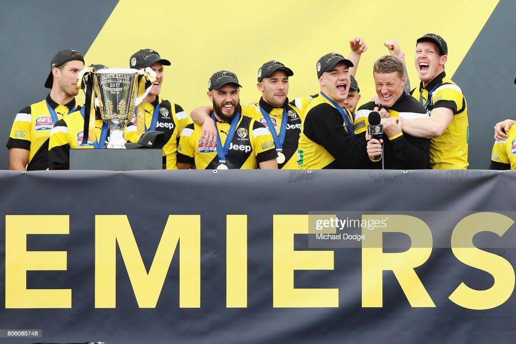 Dustin Martin of the Tigers (L) and Jack Riewoldt hug Tigers head coach Damien Hardwick as players celebrate winning yesterday's AFL Grand Final, at Punt Road Oval on October 1, 2017 in Melbourne, Australia.